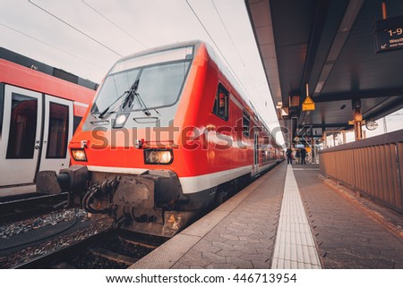 Beautiful red commuter train at railroad platform in the evening. Railway station at sunset in Nuremberg, Germany - stock photo