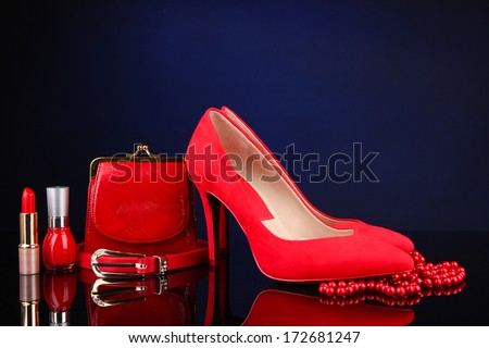 Beautiful red female accessories and cosmetics, on blue background