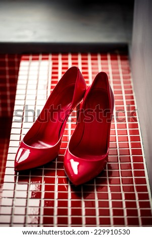 Beautiful red female shoes on red background - stock photo