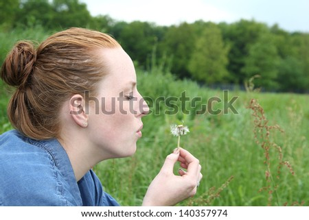 Beautiful red girl blowing a flower