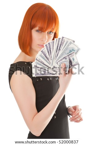 Beautiful red girl with a pack of dollars in a hand