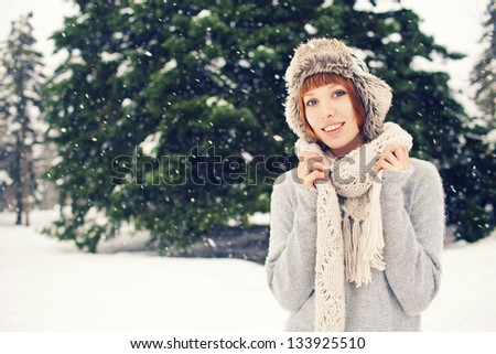Beautiful red hair girl in winter park with snow - stock photo
