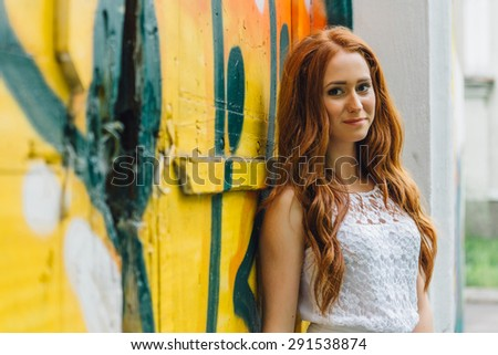 Beautiful red hair girl stands near a the multi-colored wall outdoors - stock photo