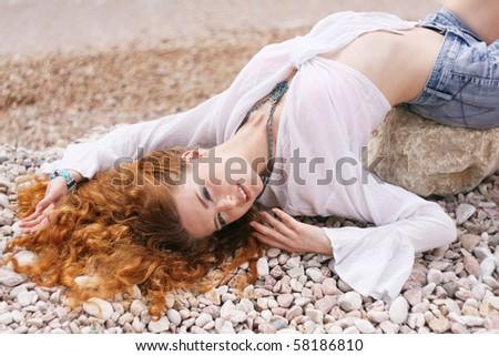 Beautiful red hair woman on the sea coast - stock photo
