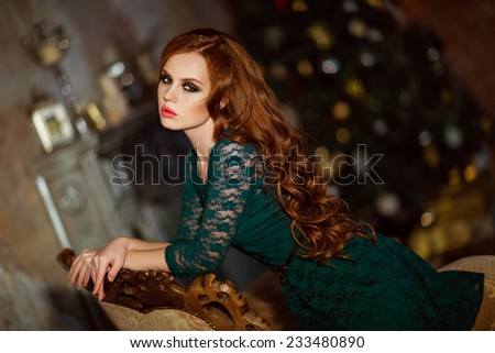 Beautiful red-haired curly girl in a green dress against the background of the Christmas tree - stock photo