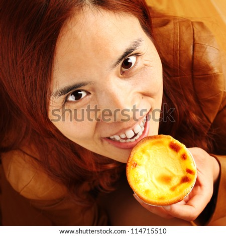 Beautiful Red Haired Girl Eating an Egg Tart - stock photo