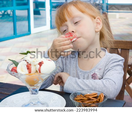 Beautiful red-haired girl eating ice cream - stock photo