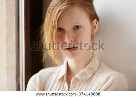 Beautiful red-haired girl face. Closeup portrait of cute red haired and freckled young woman at home. - stock photo