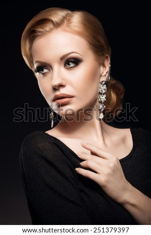 Beautiful red-haired girl in a black dress with a smooth evening haircut in the form of waves and bright makeup. Beauty face. Picture taken in the studio on a black background.
