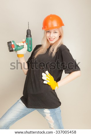 Beautiful red-haired girl in an orange construction helmet with an electric drill on a gray background.