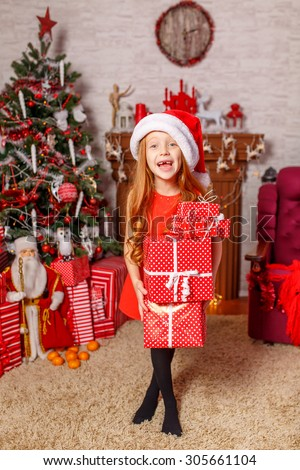 Beautiful red-haired girl in santa hat opening gift near Christmas tree. emotions - stock photo