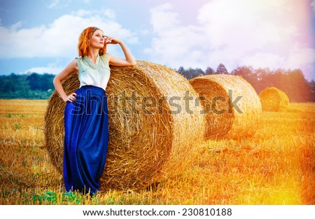 beautiful red-haired girl in the beautiful dress near the haystack - stock photo