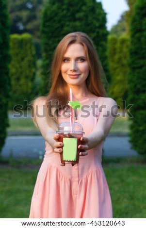 beautiful red-haired girl in the summer park with a summer drink.