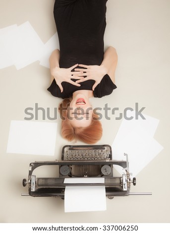 Beautiful red-haired girl lying on a gray background next to the typewriter. - stock photo