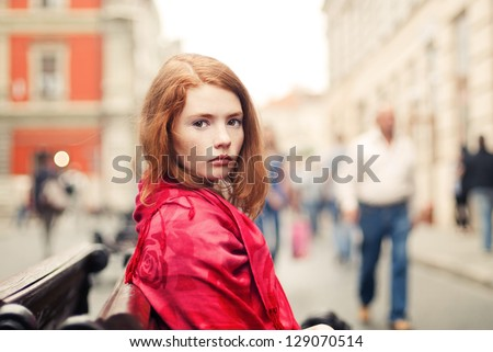 beautiful red-haired girl on a city street - stock photo