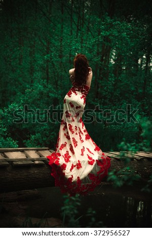 Beautiful red-haired girl on the stunning bridge in red dress