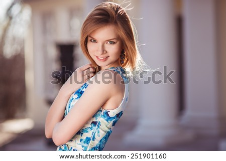 Beautiful red-haired girl posing smiling in the frame. Close-up portrait. - stock photo