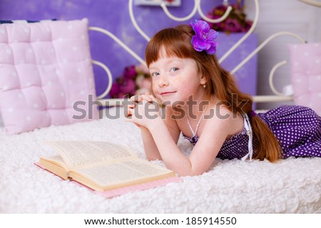 beautiful red-haired girl reading a book room - stock photo