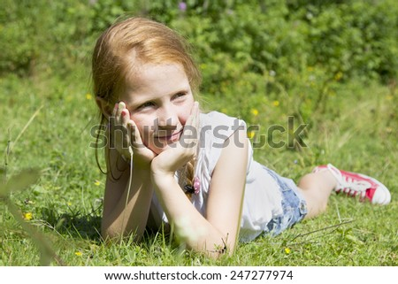 beautiful red-haired girl  sitting in the meadow and smile
