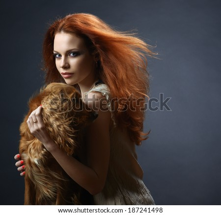 beautiful red-haired girl with a dog in the dark blue background - stock photo