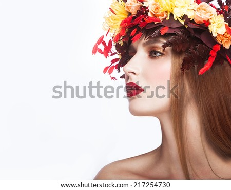 Beautiful red-haired girl with bright autumn wreath of leaves and flowers. Beauty face. Picture taken in the studio on a white background.