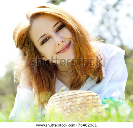 Beautiful red-haired girl with hat at the park. - stock photo