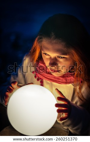 beautiful red-haired seer looks into the crystal ball. outdoors at night. - stock photo