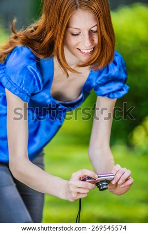 Beautiful red-haired smiling young woman in a blue blouse photographed by the camera, against green summer city park. - stock photo