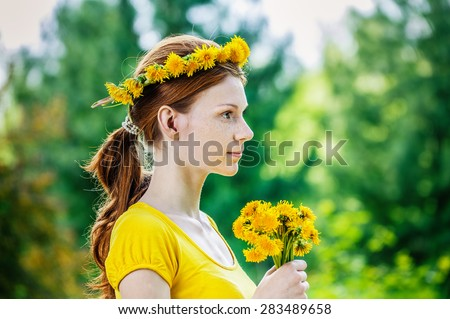 Beautiful red-haired smiling young woman in yellow blouse with a wreath and a bouquet of dandelions on a green background of summer city park. - stock photo