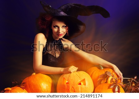 Beautiful red-haired witch casts a spell over pumpkins. Halloween. - stock photo