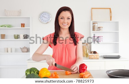 Beautiful red-haired woman cutting some vegetables in the kitchen in her apartment