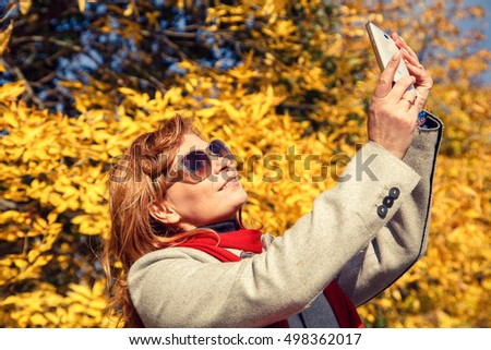 Beautiful red-haired woman doing selfie in autumn park.