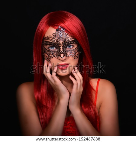 Beautiful red haired woman in carnival mask over black background - stock photo