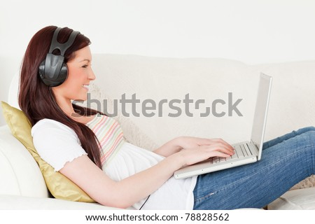 Beautiful red-haired woman listening to music with headphones while relaxing with her laptop in the living room