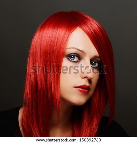 Beautiful red haired woman over dark gray background - stock photo