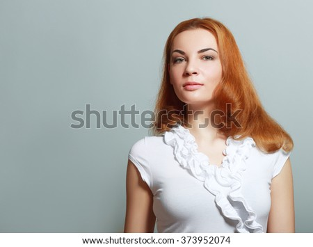 Beautiful red haired woman over gray background - stock photo