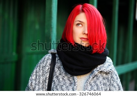 Beautiful red haired woman posing outdoors. Street style.