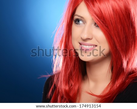 Beautiful red haired woman posing over blue background