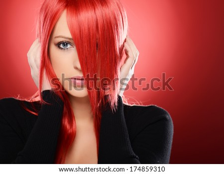 Beautiful red haired woman posing over red background