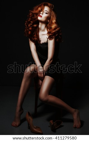 Beautiful red haired woman relaxing in black silk peignoir, take off her shoes over black background.