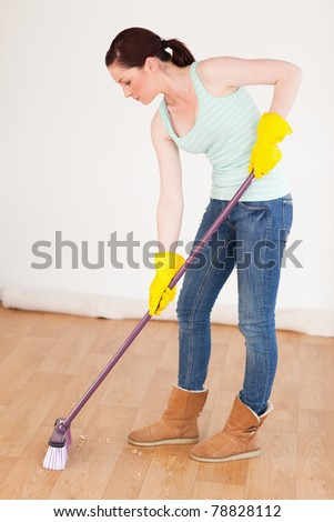 Beautiful red-haired woman sweeping the floor at home - stock photo
