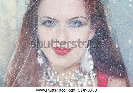 Beautiful red-haired woman under a veil