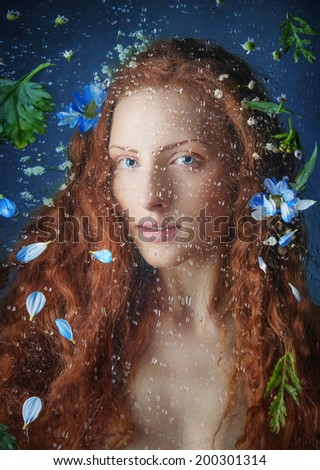 Beautiful Red haired Young Woman behind the Window with Water Drops on it and flowers - stock photo