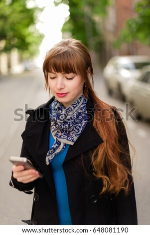 Beautiful red-haired young woman walking down the city street on a sunny day, using the Mobile Phone.