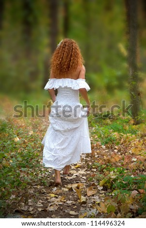 Beautiful red-haired young woman, wearing in white dress or bride go to the forest, view from the back. The rear view. - stock photo