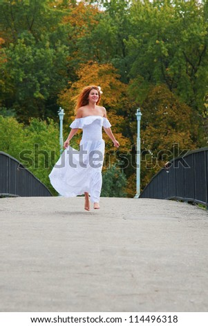 Beautiful red-haired young woman, wearing in white dress or bride running across a bridge in the autumn park in an urban neighborhood. Her face happy, she almost flying