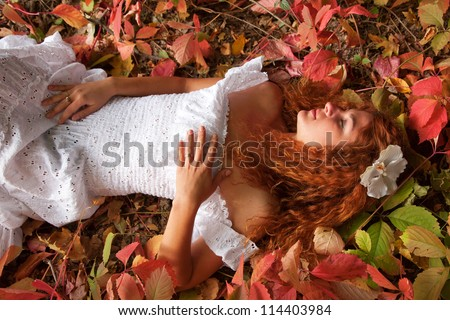Beautiful red-haired young woman, wearing in white dress or the bride and decoration in form of flower on her head lying among red leaves in autumn forest.and dreaming. symbol of autumn