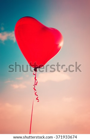 beautiful red heart shape balloon against sky with clouds - stock photo