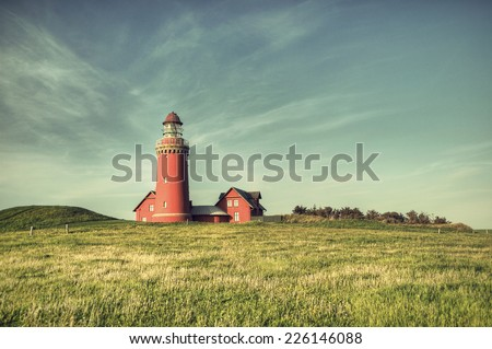 beautiful red Lighthouse Bovbjerg Fyr with green grass and blue sky in vintage style, HDR, Danish North Sea coast, Jutland, Denmark, Europe - stock photo