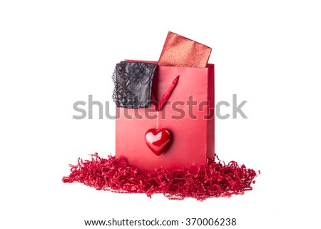 Beautiful red love present bag with black lingerie and envelope. Sexy lace underwear for girlfriend woman or sweetheart. Nice idea for e.g. Valentine's Day or birthday. Isolated on white background - stock photo